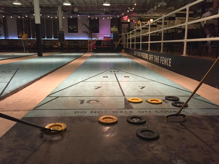 Naturally, your buds will find a bar that also includes sports. Like shuffleboard.